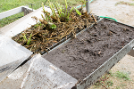 Left: The soil in the pan on the left is covered by old crop residue (stalks and leaves) and the green plants are cover crops, used to replenish soil. Right: The soil is naked. Message: Don't farm naked, or your soil will erode!